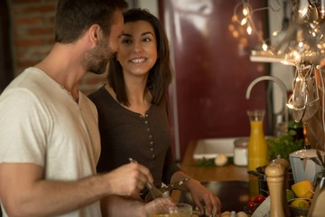 Couple talking while preparing food in  kitchen