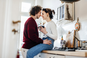 A young couple hugging in a kitchen.