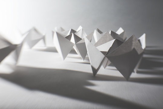 Folded white paper fortune tellers casting long shadows