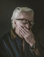 Portrait of an older man yawning