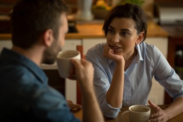 Couple talking while having coffee at table