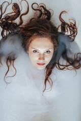 Portrait of a beautiful redhead with freckles having a milk bath