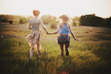 Two female friends run on a field