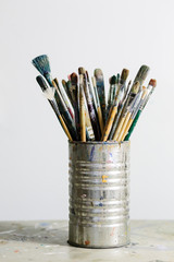 artist brushes in can near blank canvas