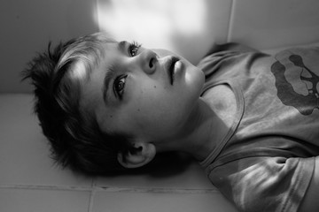 Black and white close up of thoughtful boy laying on bathroom floor.