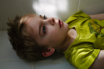 Close up of boy lying in dappled light on bathroom floor.