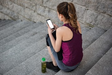 Woman using mobile phone on steps