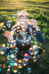 Young woman sitting on meadow grass blowing soap bubbles