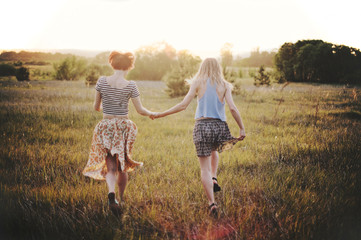 Two young female friends run on a field