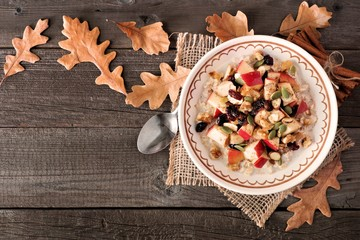Autumn oatmeal with apples, cranberries, seed and nuts, top view on wood with fall leaves