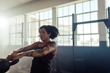Fitness woman swinging a kettlebell at gym
