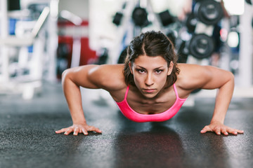 Woman working out doing pushup in the gym