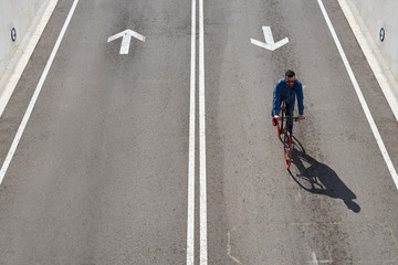 From above, young man ride his bicycle on roadway