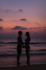 Romantic couple on the beach at colorful sunset in background