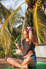 Beautiful woman drinking beer at the beach