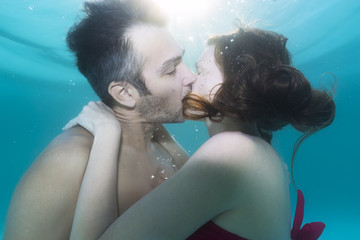 Man and a woman kissing underwater in the swimming pool