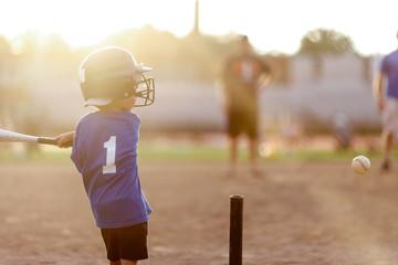 young boy swinging at baseball with bat