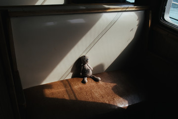 A worn and loved handmade rabbit toy sits in a shaft of sunlight on a traditional Istanbul ferryboat.