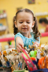 Little Girl Reaches In To Select Paint Brush