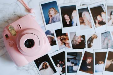 A pink camera and polaroid photographs