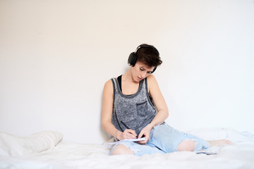 Woman sitting on bed in headphones