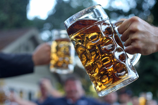 Men toasting beer with big, glass steins