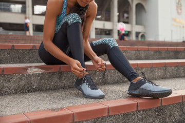 Closeup of female sport fitness runner getting ready for jogging outdoors tying the shoe laces