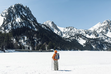 Back view of a mountaineer on the snowy landscape.