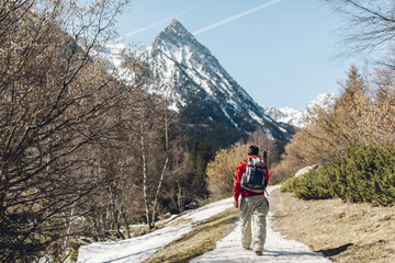Back view of the male mountaineer walking to the snowy National Park