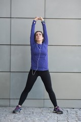 Woman performing stretching exercise outside building