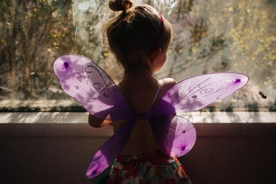 Little girl with butterfly wings in window