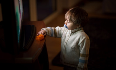 Portrait of a 1 year old boy in front of a tv screen
