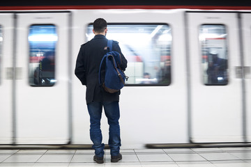 Young man standing in front of subway train