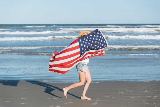 Woman holding American flag while running on the beach