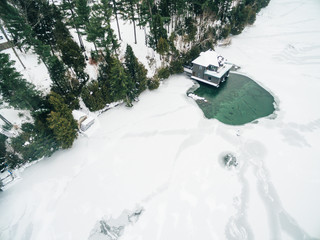 Aerial drone image of a boathouse on a frozen lake
