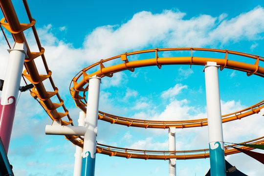 Tracks of orange roller coaster against blue sky