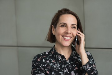 Woman talking on mobile phone outside building