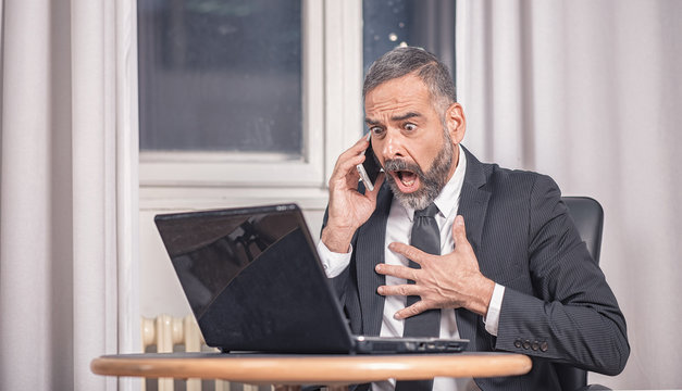 Senior business man shocked with an email he receives on his laptop, office environment