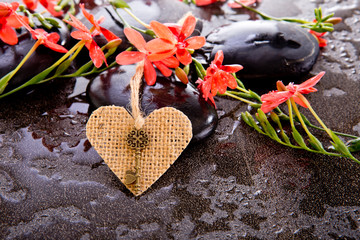Orange Red Freesia Laxa flowers with black massage stones and burlap heart shape with brass key