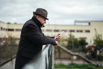 Portrait of a senior man using smartphone outdoor