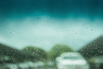 Beautiful cover of rain drops on glass with blur car park background