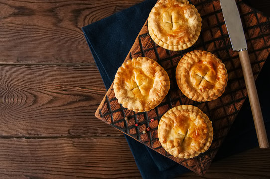 Mini meat pies from flaky dough on a wooden board over wooden background.