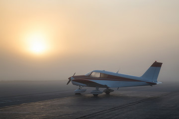 Beautiful foggy sunrise at the Airport with an Airplane parked at the apron. Wall mural