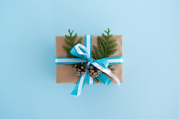 Gift box wrapped of craft paper, blue and white ribbons and decorated fir branches and pinecones on the blue background, top view. Christmas present.