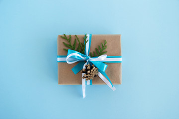 Gift box wrapped of craft paper, blue and white ribbons and decorated fir branches and pinecone on the blue background, top view. Christmas present.