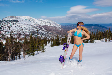 Young woman in swimsuit with snowboard on the slope