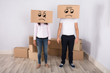 Sad Couple Wearing Cardboard Boxes