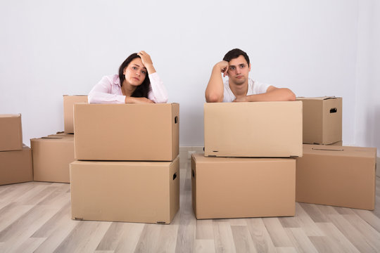 Worried Couple Sitting Near The Cardboard Boxes