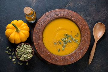 Pumpkin cream-soup with addition of pumpkin seeds and spices, view from above, studio shot