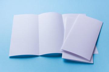Leaflet blank tri-fold white paper brochure mockup on blue background